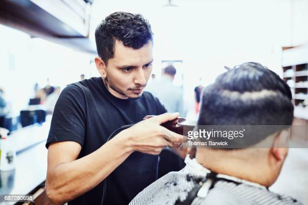 Barber using trimmer to cut mans hair in barber shop