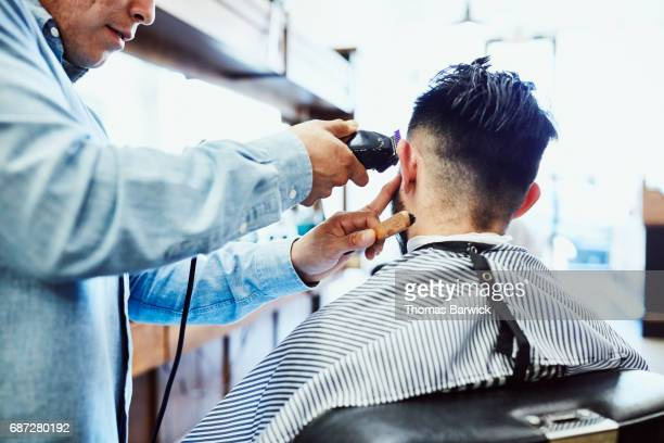Barber using trimmer while cutting clients hair in barber shop