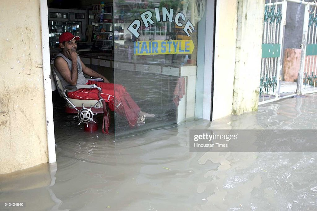 A Barber waiting in his flooded shop for customer during the heavy rain in Mira-Bhyander at Mumbai suburban on August 1, 2005 in Mumbai, India.