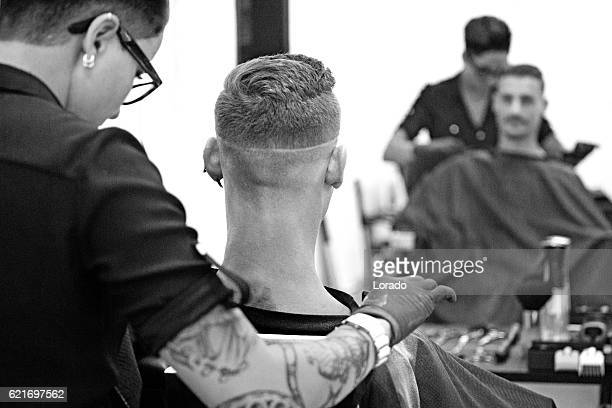 Barber working on a clients hair with mirror