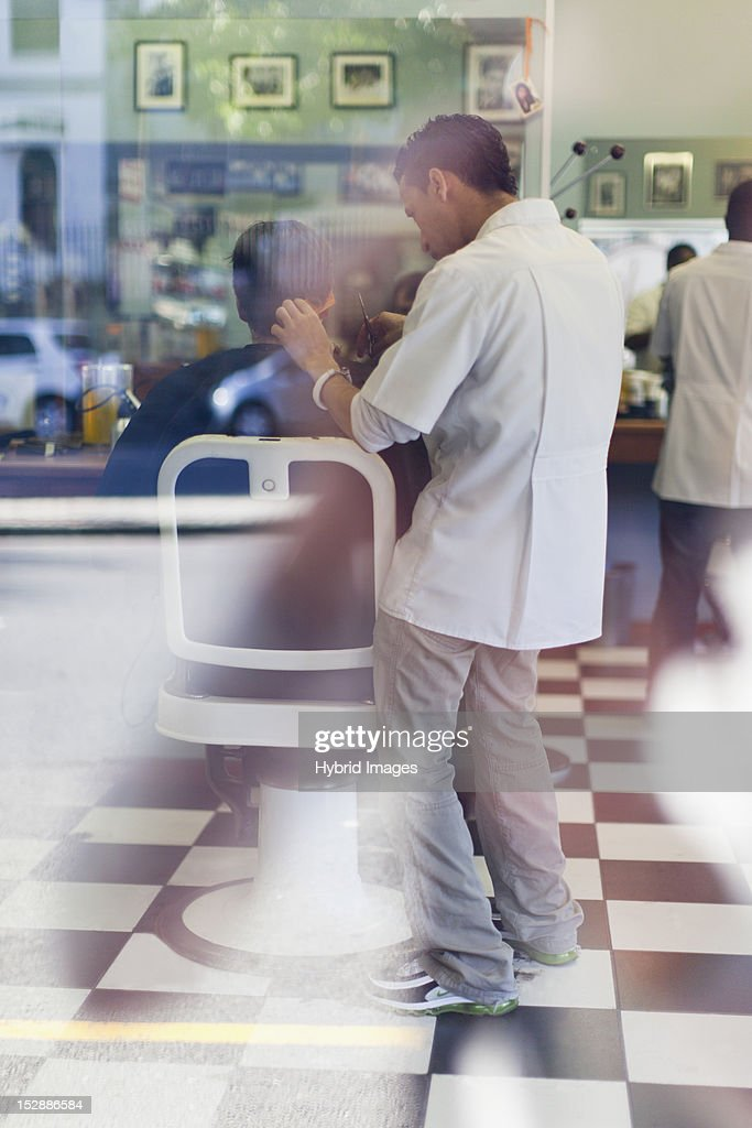 Barber working on client in shop : Stock Photo