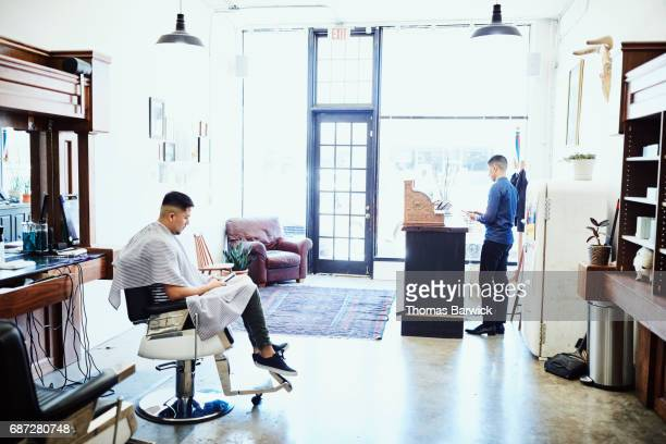 Barber working on smartphone in shop while customer waits to finish hair cut