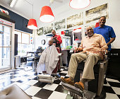 Barbers and customers smiling in retro barbershop