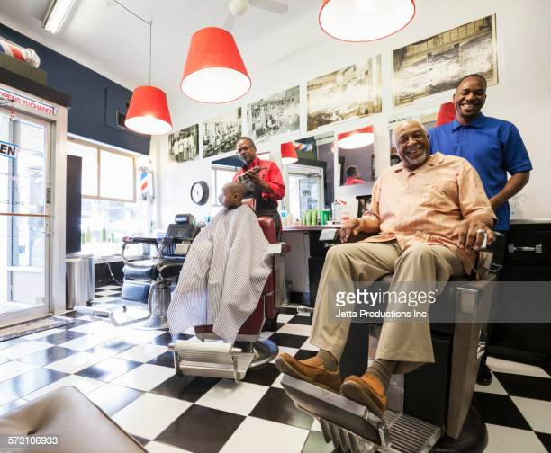 Barbers and customers smiling in retro barbershop
