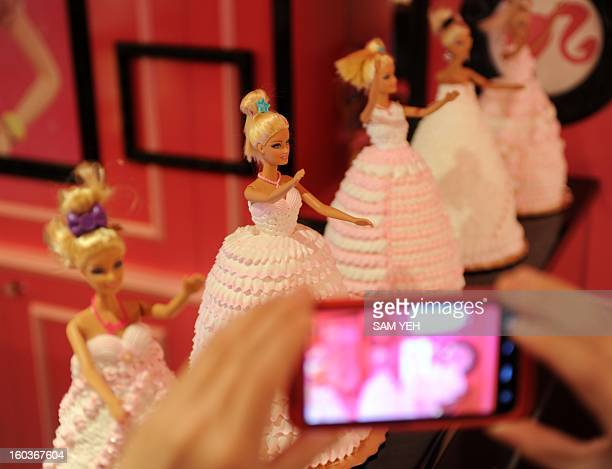 A Barbie fan takes pictures of the cakes during the opening ceremony of a Barbiethemed restaurant in Taipei on January 30 2013 With hot pink sofas...