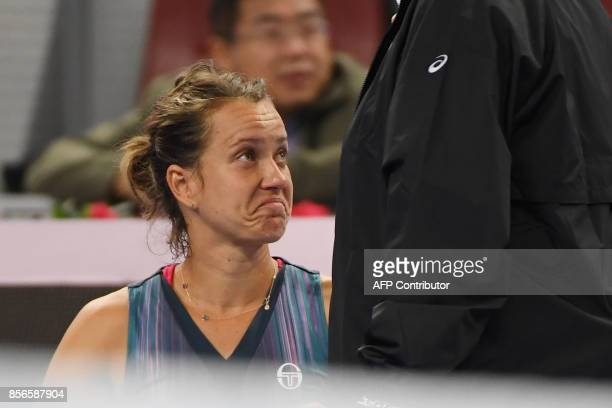 Barbora Strycova of the Czech Republic reacts after Garbine Muguruza of Spain retired from their women's singles match at the China Open tennis...