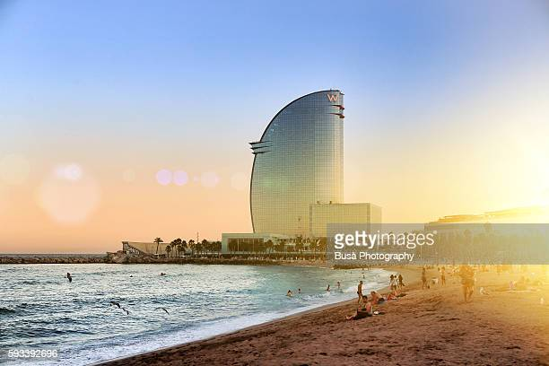 W Barcelona, a luxury highrise boutique hotel designed by architect Ricardo Bofill along the Barceloneta boardwalk, at sunset. Barcelona, Spain