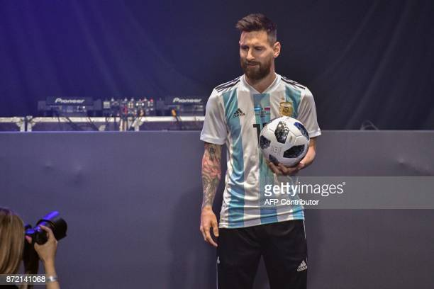 TOPSHOT Barcelona and Argentina forward Lionel Messi poses with the official match ball for the 2018 World Cup football tournament named 'Telstar 18'...