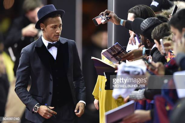 Barcelona and Brazils forward Neymar signs autographs on the red carpet as he arrives for the 2015 FIFA Ballon d'Or award ceremony at the...