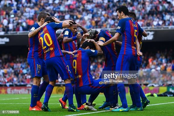 Barcelona are hit by objects thrown from the seats after Lionel Messi of FC Barcelona scores his team's third goal from the penalty spot during the...
