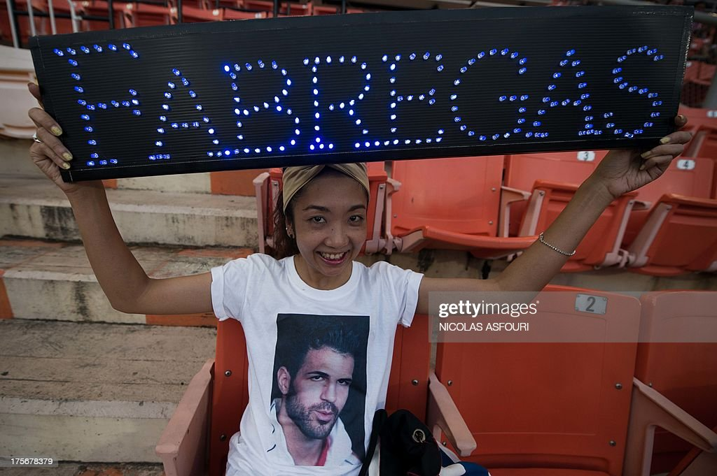 A Barcelona FC fan holds an electronic light board with the inscription ''FABREGAS'' and wears a T-shirt with a picture of the Barcelona football player Cesc Fabregas at the Rajamangala football stadium ahead of FC Barcelona training session in Bangkok on August 6, 2013. Barcelona football team will play an exhibition match with Thailand national team at the Rajamangala National Stadium in Bangkok on August 7. AFP PHOTO/ Nicolas ASFOURI