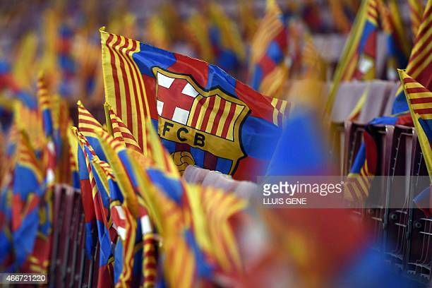 Barcelona football club flags are waved by supporters before the UEFA Champions League round of 16 football match FC Barcelona vs Manchester City at...