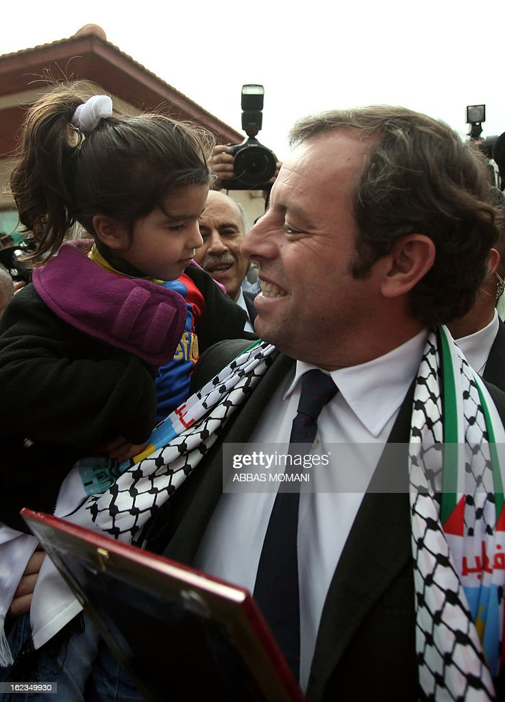 FC Barcelona football club's president Sandro Rosell (R) greets a young Palestinian Barcelona club football fan prior to giving a press conference in the West bank city of Ramallah, on February 22, 2013. Rosell is visiting to promote a football match between Israel and the Palestinians with players from both sides of the conflict as a step towards Middle East peace. AFP PHOTO/ABBAS MOMANI