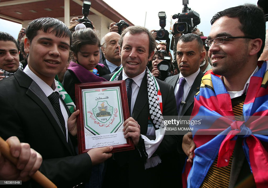 FC Barcelona football club's president Sandro Rosell (C) is greeted by Palestinian Barcelona club football fans, prior to giving a press conference in the West bank city of Ramallah, on February 22, 2013. Rosell is visiting to promote a football match between Israel and the Palestinians with players from both sides of the conflict as a step towards Middle East peace.