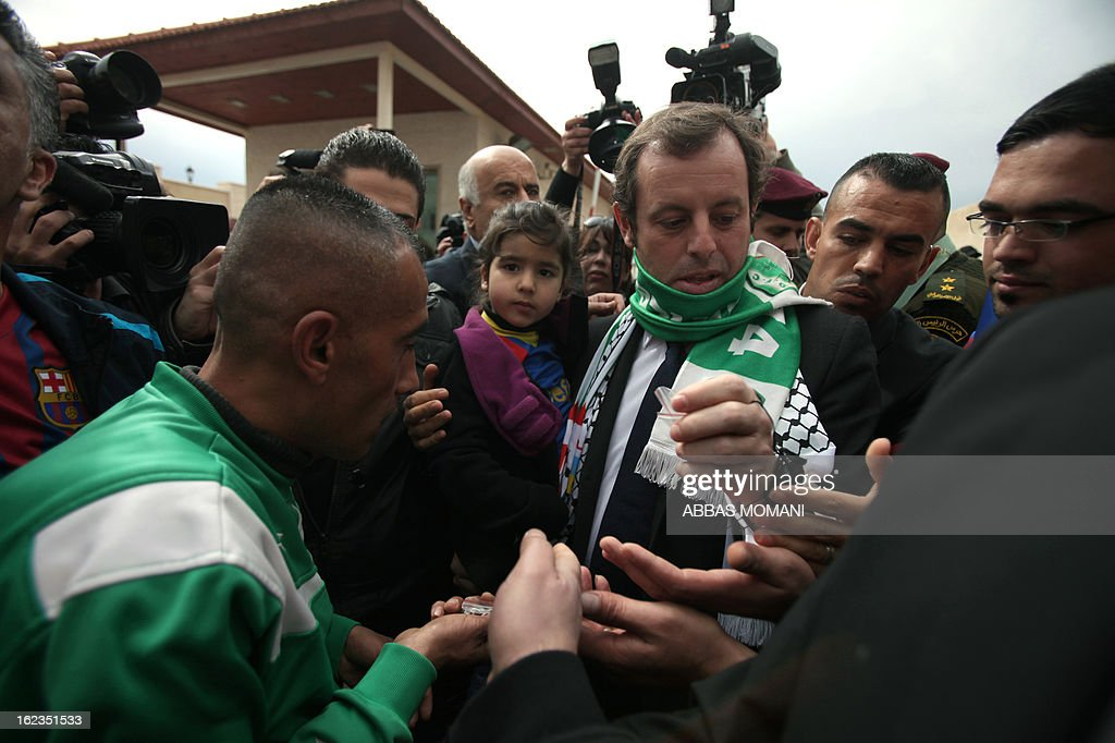 FC Barcelona football club's president Sandro Rosell (C-R) is greeted by Palestinian Barcelona football fans, prior to giving a press conference in the West bank city of Ramallah, on February 22, 2013. Rosell is visiting to promote a football match between Israel and the Palestinians with players from both sides of the conflict as a step towards Middle East peace. AFP PHOTO/ABBAS MOMANI