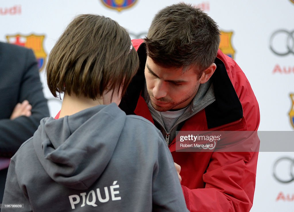 Barcelona football player <a gi-track='captionPersonalityLinkClicked' href=/galleries/search?phrase=Gerard+Pique&family=editorial&specificpeople=227191 ng-click='$event.stopPropagation()'>Gerard Pique</a> autographs a jersey during a Audi presentation during which Barcelona FC players received new Audi cars for the 2012-2013 season at Camp Nou on November 21, 2012 in Barcelona, Spain.