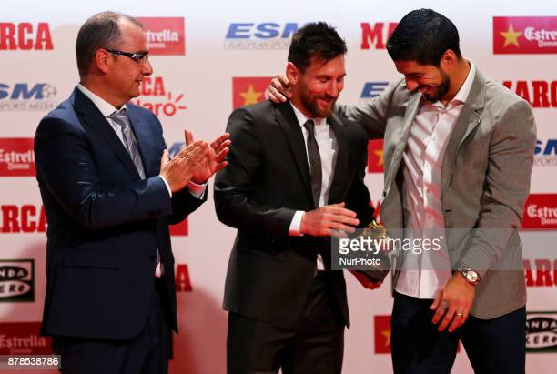 Barcelona football player Luis Suarez gives the Golden Boot award to Lionel Messi at the Old Estrella Damn Factory on November 24 2017 in Barcelona...