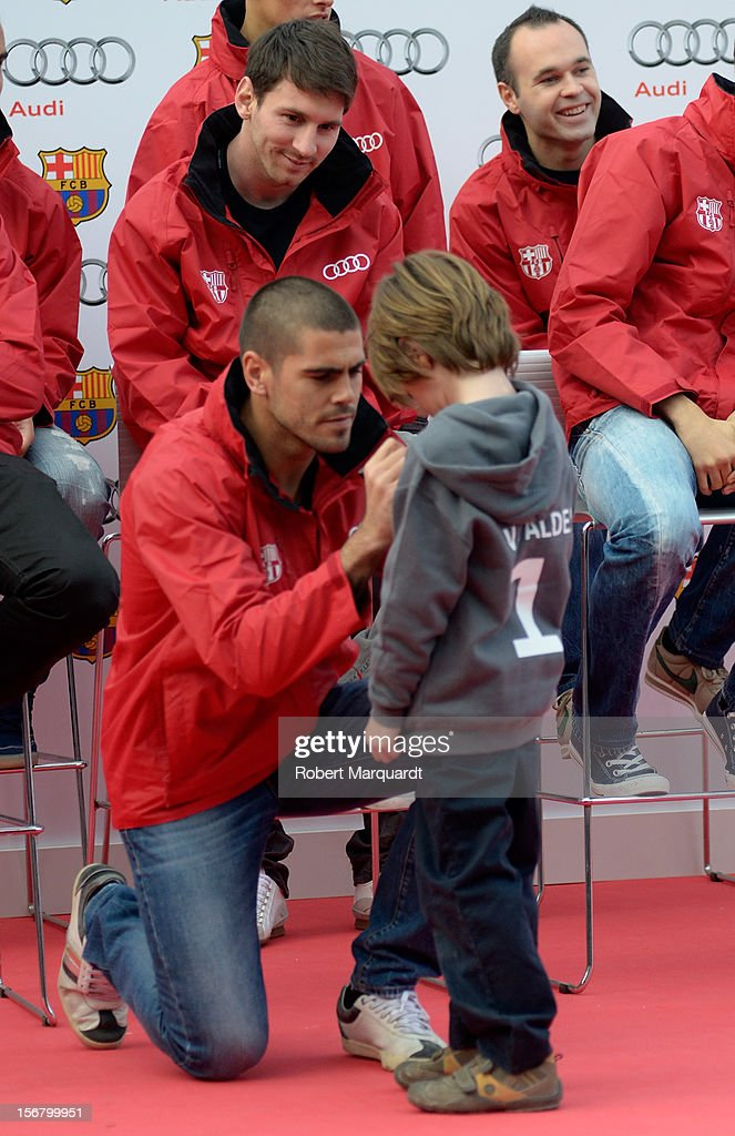 Barcelona football player Victor Valdes autographs a jersey while Lionel Messi looks on during an Audi presentation during which Barcelona FC players received new Audi cars for the 2012-2013 season at Camp Nou on November 21, 2012 in Barcelona, Spain.
