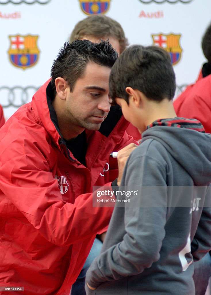 Barcelona football player <a gi-track='captionPersonalityLinkClicked' href=/galleries/search?phrase=Xavi+Hernandez+-+Soccer+Player&family=editorial&specificpeople=2834438 ng-click='$event.stopPropagation()'>Xavi Hernandez</a> autographs a jersey during an Audi presentation during which Barcelona FC players received new Audi cars for the 2012-2013 season at Camp Nou on November 21, 2012 in Barcelona, Spain.