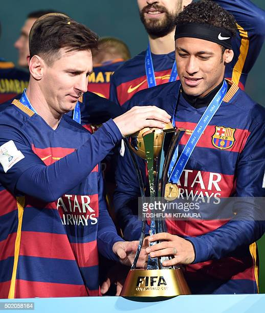 Barcelona forward Lionel Messi and Neymar hold the FIFA Club World Cup trophy on the podium of the Club World Cup football tournament final in...