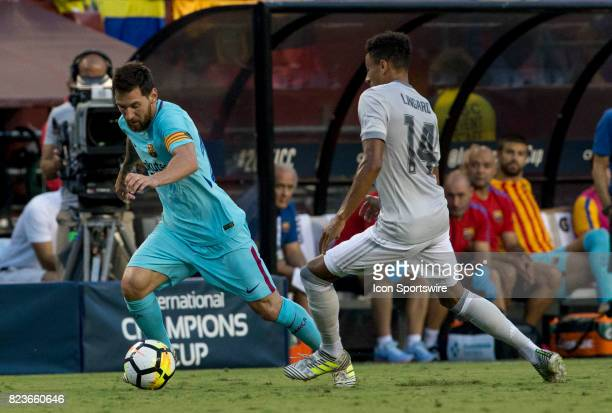 Barcelona forward Lionel Messi pulls away from Manchester United midfielder Jesse Lingard during an International Champions Cup match between...