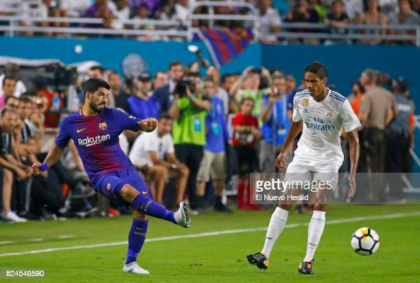 Barcelona forward Luis Suarez passes the ball against Real Madrid defender Raphael Varane during the first half of the ''El Clasico Miami''...