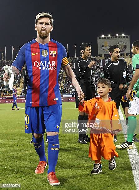 FC Barcelona Lionel Messi holds the hands of Afghan boy Murtaza Ahmadi on the pitch before the start of a friendly football match against Saudi...
