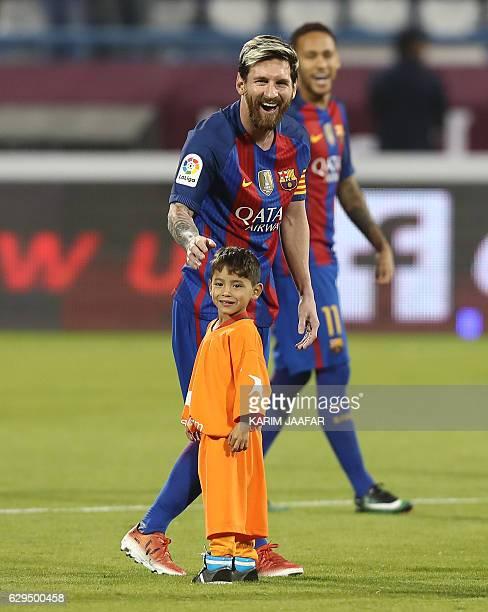 Barcelona Lionel Messi talks to Afghan boy Murtaza Ahmadi on the pitch before the start of a friendly football match against Saudi Arabia's AlAhli FC...