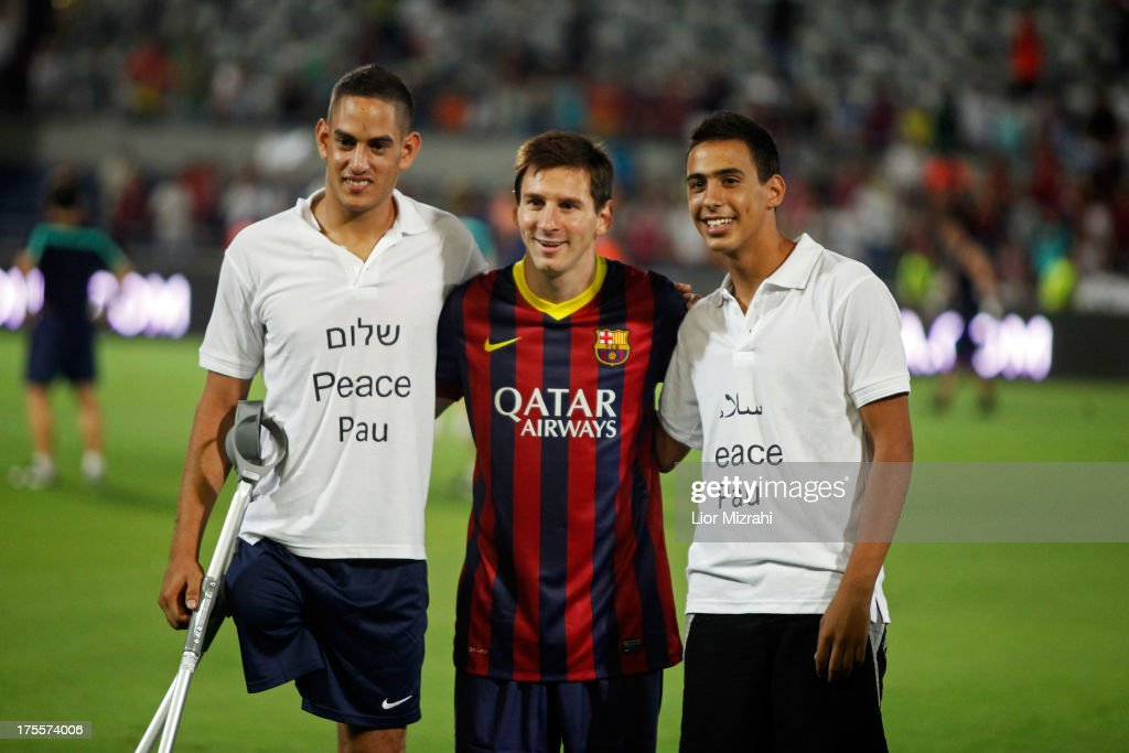 FC Barcelona player Lionel Messi poses for a photo with Israeli citizen Asael Shabo (L) from the West Bank settlement of Kdomim and Palestinian Mohammad Roman from the West Bank city of Jericho during a training session on August 4, 2013 in Tel Aviv, Israel. Members of the FC Barcelona squad have travelled to the Middle East to visit Israel and the West Bank as part of a two-day 'peace tour'.