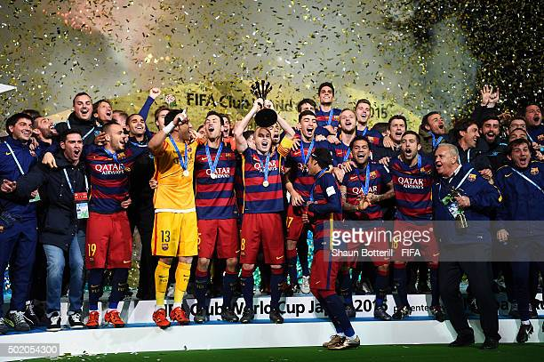 Barcelona players and coaching staff celebrate as captain Andres Iniesta of Barcelona lifts the trophy following their 30 victory during the FIFA...