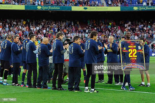 Barcelona players and staff members acknowledge their teammate Eric Abidal as he leaves the picth holding his jersey after he played his last match...