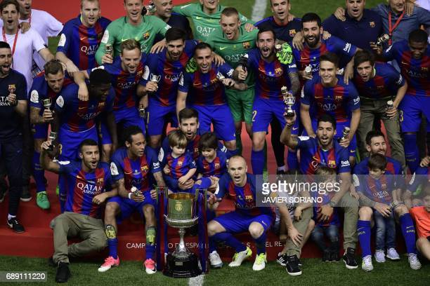 TOPSHOT Barcelona players and staff pose with the trophy at the end of the Spanish Copa del Rey final football match FC Barcelona vs Deportivo Alaves...