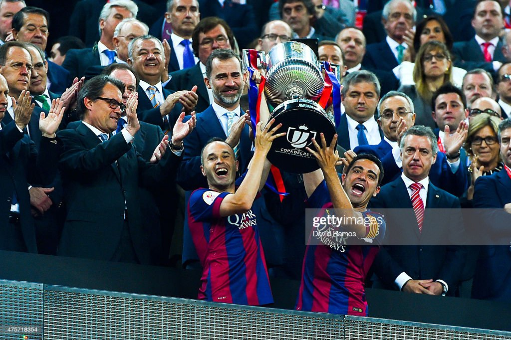 FC Barcelona players <a gi-track='captionPersonalityLinkClicked' href=/galleries/search?phrase=Andres+Iniesta&family=editorial&specificpeople=465707 ng-click='$event.stopPropagation()'>Andres Iniesta</a> (L) and <a gi-track='captionPersonalityLinkClicked' href=/galleries/search?phrase=Xavi+Hernandez+-+Soccer+Player&family=editorial&specificpeople=2834438 ng-click='$event.stopPropagation()'>Xavi Hernandez</a> of FC Barcelona celebrate with the trophy after winning the Copa del Rey Final match between FC Barcelona and Athletic Club at Camp Nou on May 30, 2015 in Barcelona, Spain.