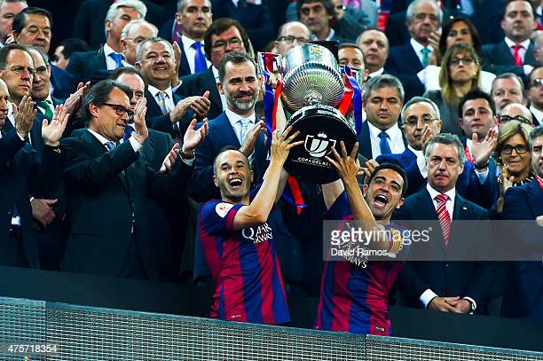 Barcelona players Andres Iniesta and Xavi Hernandez of FC Barcelona celebrate with the trophy after winning the Copa del Rey Final match between FC...
