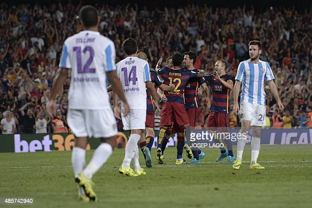 Barcelona players celebrate after scoring the opener during the Spanish league football match FC Barcelona vs Malaga CF at the Camp Nou stadium in...