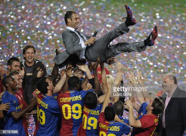 Barcelona players lift their coach Pep Guardiola in celebration of their Spanish league title 2009 after their Spanish League football match against...