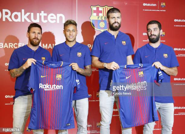 FC Barcelona players Lionel Messi Neymar Gerard Pique and Arda Turan show off the team's shirt for the 20172018 season at Rakuten Inc's Tokyo...
