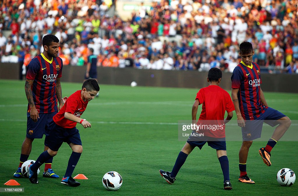 FC Barcelona players Neymar (R) and Daniel Alves in action with local Israeli children during a training session on August 4, 2013 in Tel Aviv, Israel. Members of the FC Barcelona squad have travelled to the Middle East to visit Israel and the West Bank as part of a two-day 'peace tour'.