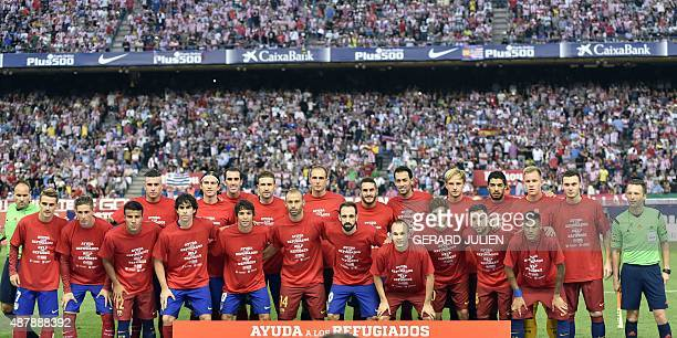 Barcelona players pose with a jersey reading 'Help the refugees' prior to the Spanish league football match Club Atletico de Madrid vs FC Barcelona...