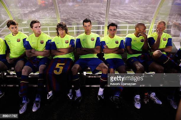 Barcelona players sit on the bench before the start of the international friendly soccer match against Los Angeles Galaxy at the Rose Bowl on August...
