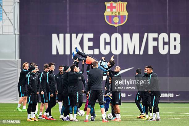 Barcelona players throw a young fan in the air after he and his friends ran onto the training pitch during a Barcelona training session ahead of the...