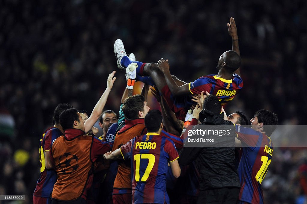 FC Barcelona players toss teammate Eric Abidal up in the air after defeating Real Madrid in the UEFA Champions League Semi Final second leg match between Barcelona and Real Madrid, at the Camp Nou on May 3, 2011 in Barcelona, Spain.