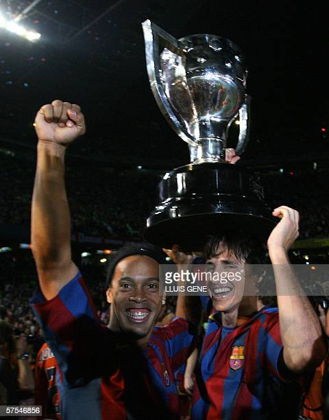 Barcelona's Brazilian Ronaldinho and compatriot Edmilson poses with the league cup after beating Espanyol and winning the Spanish league at the Camp...