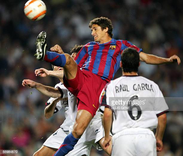 FC Barcelona's Brazilian Edmilson vies for the ball with Osasuna's Izquierdo and Raul Garcia during their Spanish League football match at the Camp...