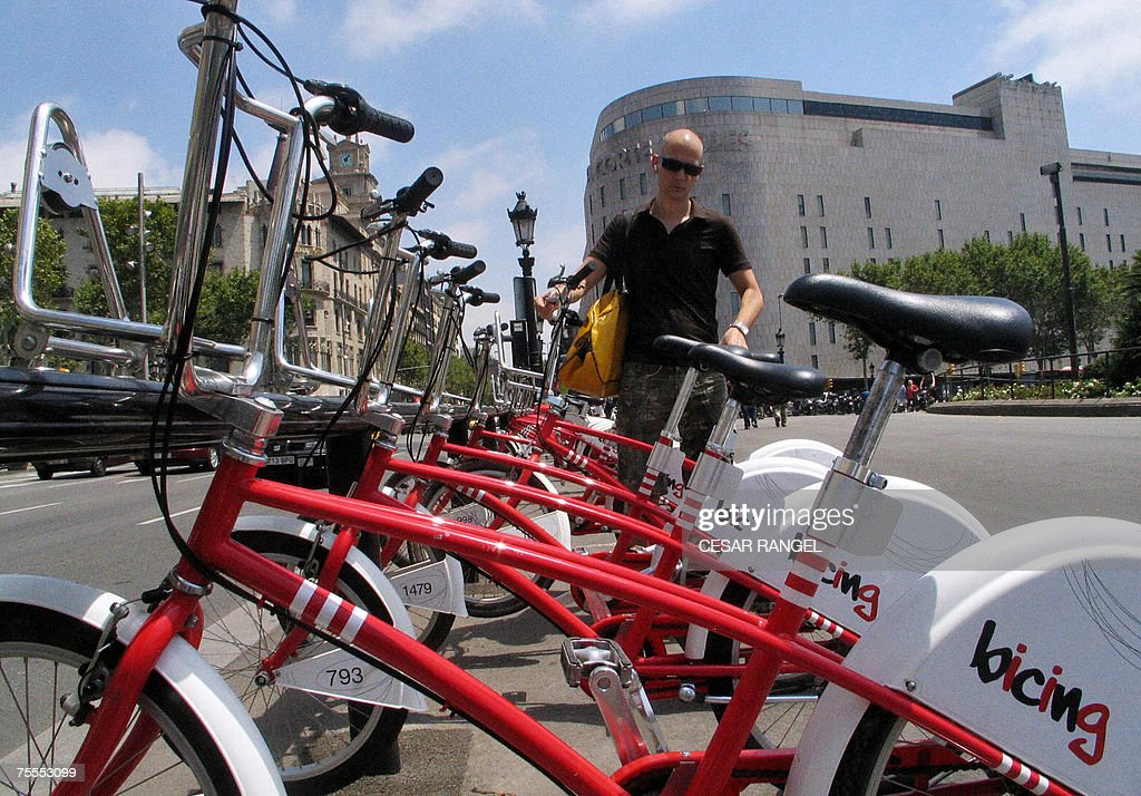 TO GO WITH AFP STORY BY MARCELO APARICIO A man takes a 'Bicing' bike for a ride a new shared bicycle service 18 July 2007 on the Plaza Catalunya in...