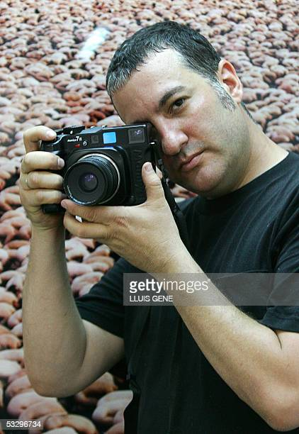 US photographer Spencer Tunick poses in front of one of his photographs 28 July 2005 in Barcelona during the presentation of his exhibition 'Corpus...
