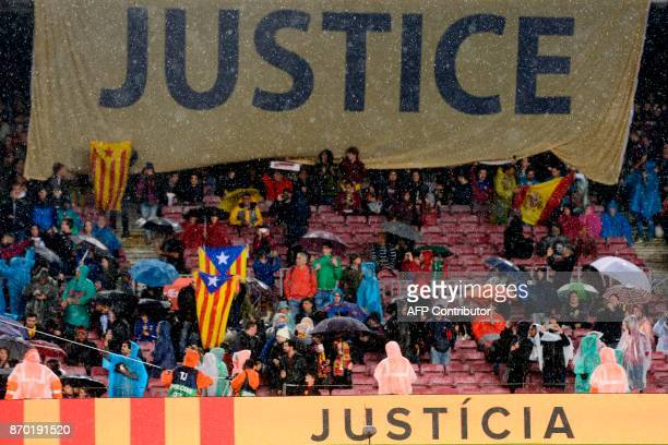 Barcelona supporters hold a banner reading 'Justice' while waving proindependence Catalan Estelada flags ahead of the Spanish league football match...