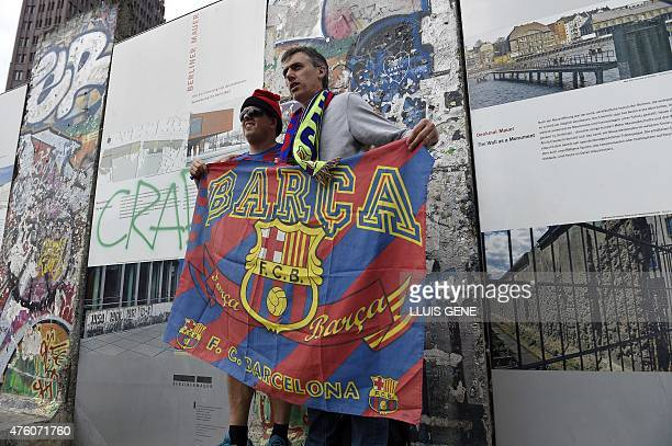 FC Barcelona supporters pose with a flag of their team in front of Berlin Wall remnants at the Potsdamer Platz in Berlin on June 6 ahead of the UEFA...