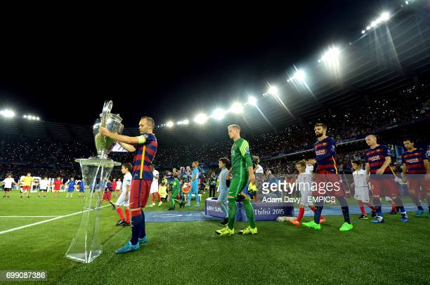 Barcelona's Andres Iniesta places the Champions League trophy on a plinth before the game