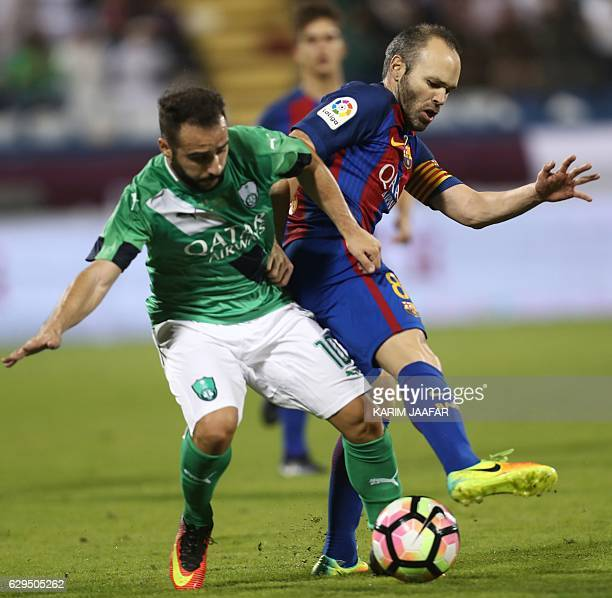 FC Barcelona's Andres Iniesta vies for the ball with AlAhly's Giannis Fetfatzidis during a friendly football match between FC Barcelona and Saudi...